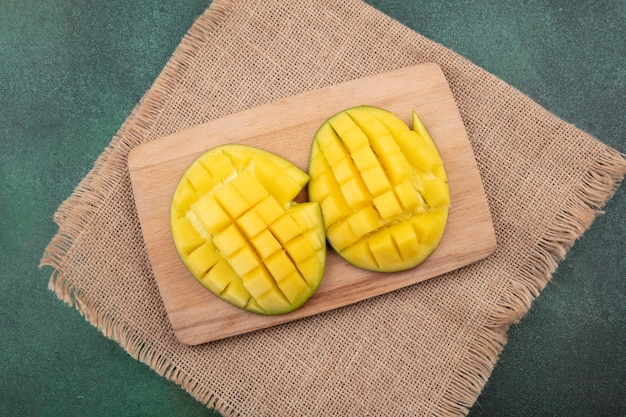 Top view of exotic fresh and yellow mango slices on wooden kitchen board on sack cloth on green