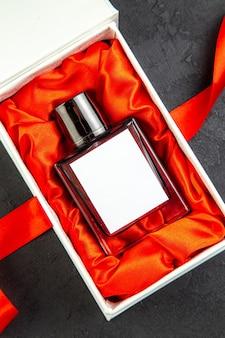 Profumo costoso vista dall'alto in una confezione elegante come regalo sul tavolo scuro