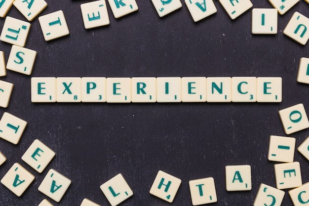 Top view of experience text with scrabble letters over black backdrop
