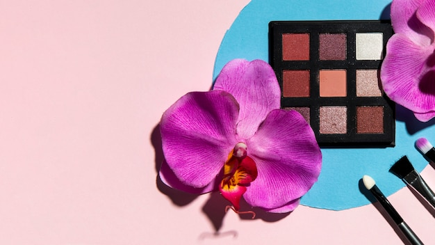 Top view of eye shadow and flowers on pink background