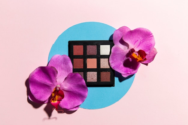 Top view of eye shadow and flowers with pink background
