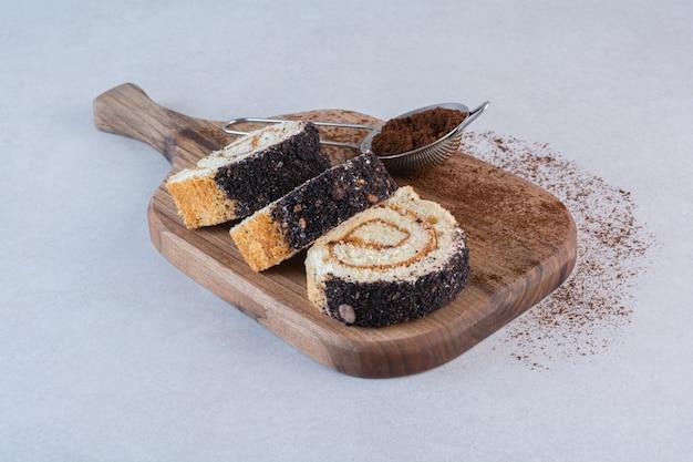 Rotolo di torta fatta in casa di vista superiore f sulla tavola di legno sopra bianco