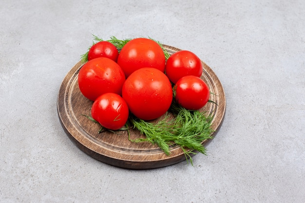 Top view of f4resh ripe tomatoes on wooden board.
