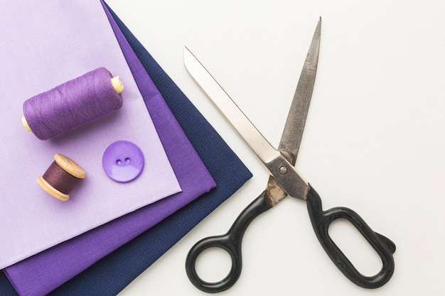 Top view of fabrics with scissors and button