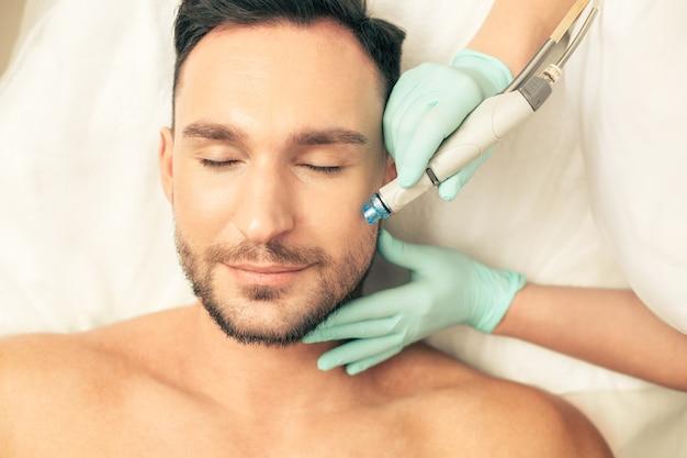 Вид сверху лицо молодого человека, лежащего с закрытыми глазами, и руки косметолога, увлажняющие его кожу лица с помощью специального инструмента