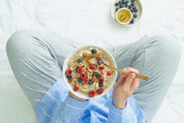 早朝ベッドに座っているオートミールのプレートを保持している平面図の顔のない女性