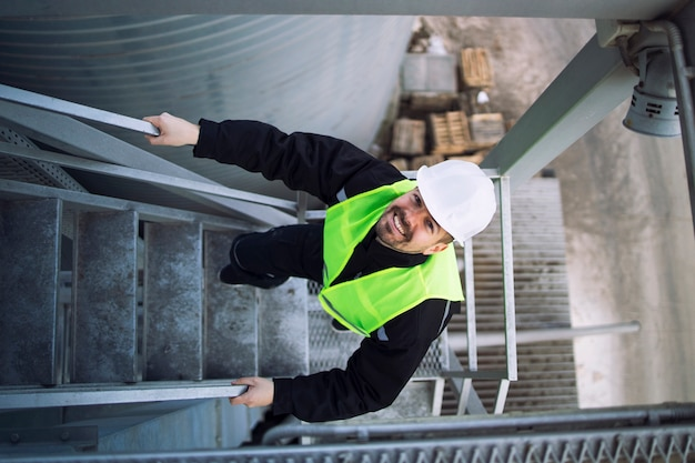 Top view of factory worker climbing metal stairs on industrial silo building