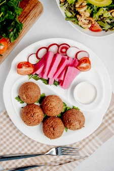 Top view of falafel with fresh vegetables on table