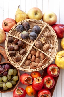 Top view to fall fruits on a wicker tray over a white wooden table