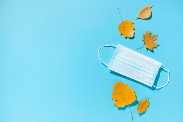 Vista dall'alto di foglie di autunno con maschera medica e copia spazio