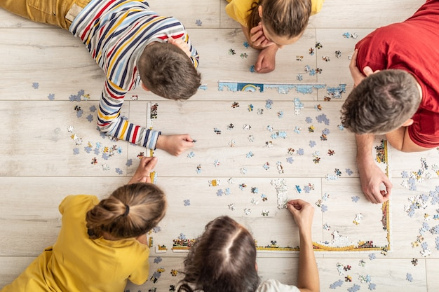 Top view of a family assembling puzzle on the floor at home.