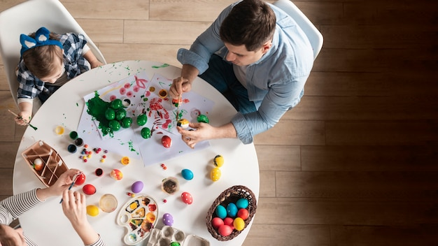 Top view family painting traditional easter eggs