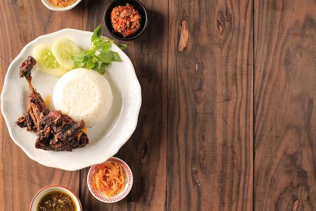 トップビューインドネシア、マドゥラ島の有名な食べ物「ベベックシンジェイ」と呼ばれるベベックはアヒルで、米、アヒル、キュウリ、バジル、ヤングマンゴーチリで構成されています。コピースペース