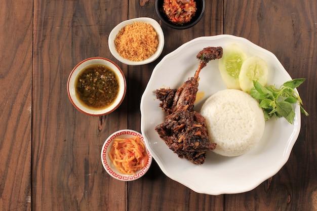 トップビューインドネシア、マドゥラ島の有名な食べ物「ベベックシンジェイ」と呼ばれるベベックはアヒルで、米、アヒル、キュウリ、バジル、ヤングマンゴーチリで構成されています