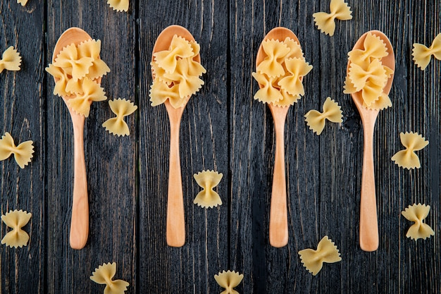 Top view farfalle pasta on black wooden background