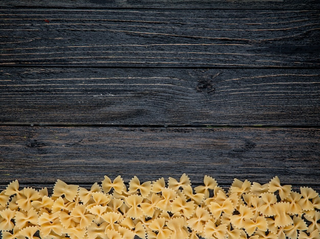 Top view farfalle pasta on the bottom with copy space on black wooden background