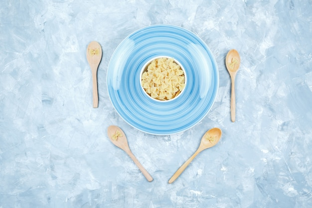Top view farfalle pasta in bowl and wooden spoons with plate on plaster background. horizontal