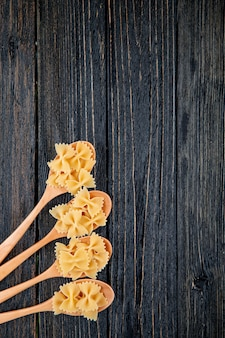 Top view farfalle pasta on the left with copy space on black wooden background