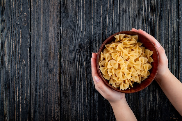Top view farfalle pasta on the right with copy space on black wooden background