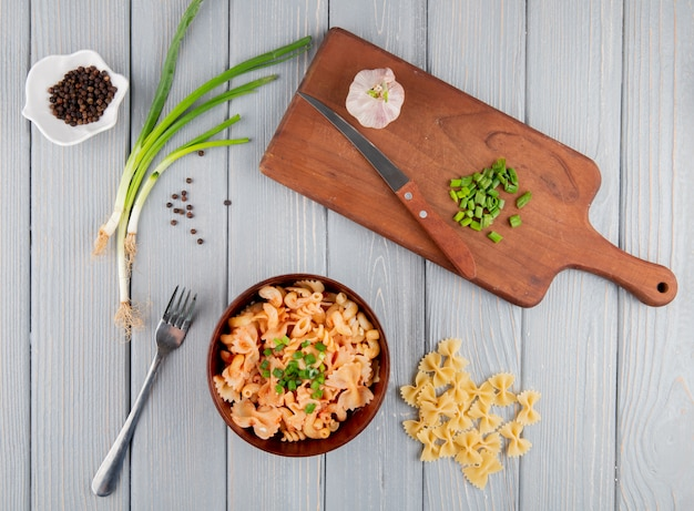 Top view of farfalle pasta with chopped green onion in a bowl wooden cutting board with knife and garlic on rustic background