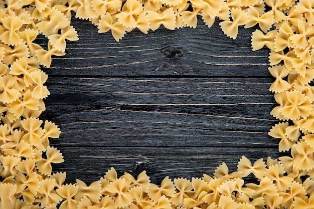 Top view farfalle pasta with copy space on black wooden background