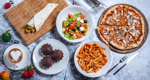 Top view fast food mix greek salad mushroom pizza chicken roll chocolate muffins penne pasta and cup of coffee on the table