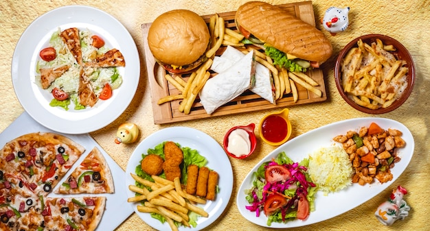 Top view fast food mix hamburger doner sandwich chicken nuggets rice vegetable salad chicken sticks caesar salad mushrooms pizza chicken ragout french fries mayo a