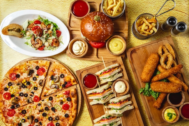 トップビューファーストフードミックスモッツァレラスティッククラブサンドイッチハンバーガーマッシュルームピザシーザーエビのサラダフライドポテトケチャップマヨネーズとチーズソースのテーブル