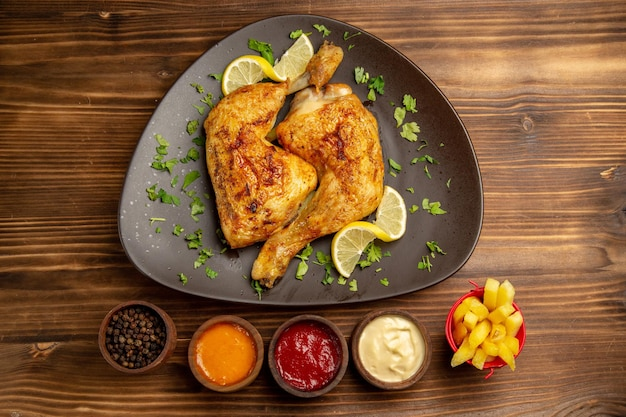 Top view fast food in the plate chicken with lemon and herbs in the plate next to the bowls of french fries black pepper and sauces on the dark table