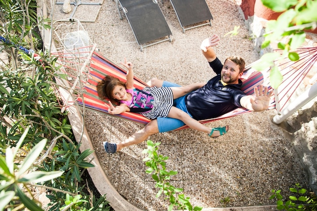 Top view of father and daughter resting on a hammock