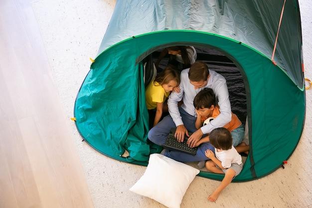 Vista dall'alto del padre seduto con bambini carini in tenda a casa e utilizzando il computer portatile. bambini adorabili che guardano film con il padre, divertendosi e rilassandosi. infanzia, tempo per la famiglia e concetto di fine settimana