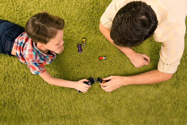 Top view of father and son lying on carpet and playing with toy cars