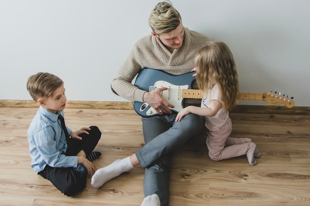 Top view of father with his guitar and his children