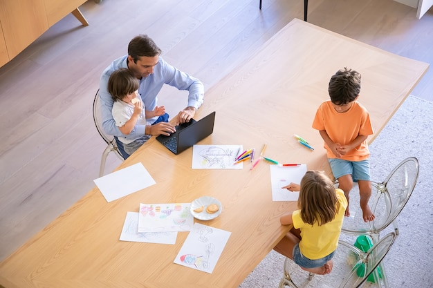 Top view of father with kids sitting at table. brother and sister drawing doodles with markers. middle-aged dad working on laptop and holding little son. childhood, weekend and family time concept