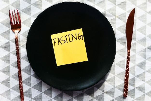 Top view of fating word on sticky note on empty plate .