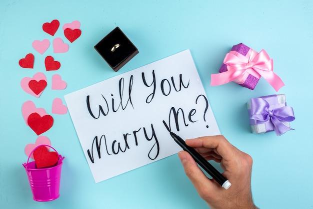 Вид сверху февральская концепция красные и розовые сердечные наклейки, разбросанные по мини-кольцу-ведру в коробке, выйдешь за меня замуж, написано на бумажном маркере в мужской руке на синем столе Premium Фотографии