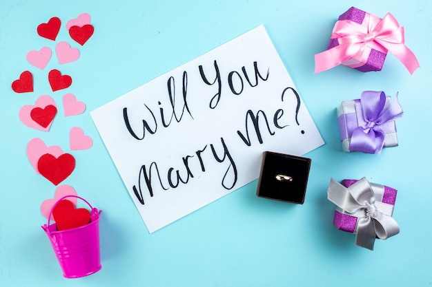 Вид сверху февральская концепция красные и розовые сердечные наклейки, разбросанные из мини-ведра, выйдешь за меня замуж написано на бумажном кольце в коробке подарки на синем столе