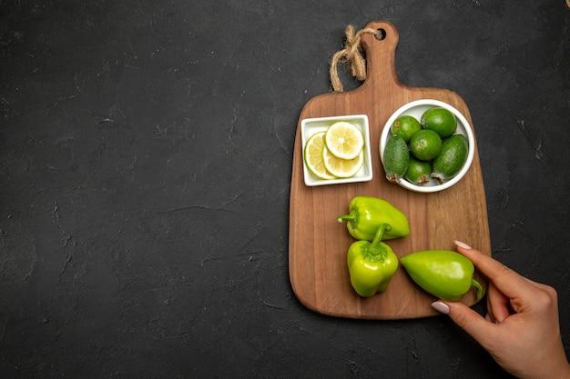 暗い表面のフルーツ柑橘類の野菜にピーマンとフェイジョアとレモンの上面図