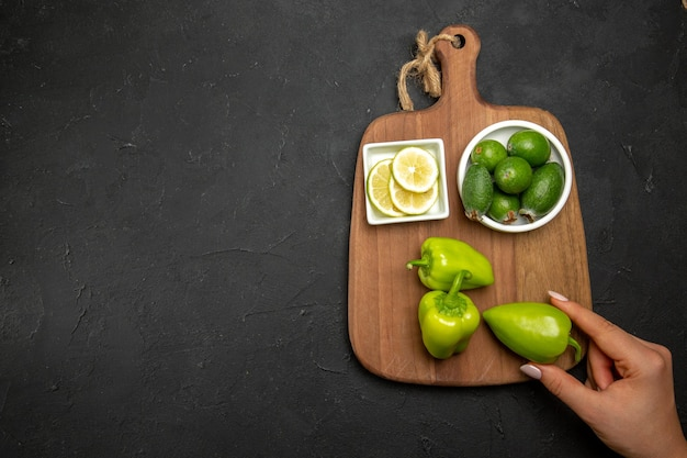 Top view feijoa and lemon with bell-peppers on dark surface fruit citrus vegetable