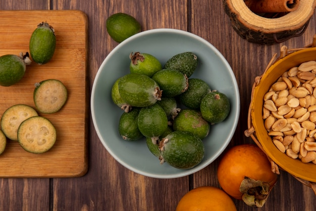 Top view of feijoas on a bowl with slices of feijoas on a wooden kitchen board with peanuts on a bucket on a wooden background