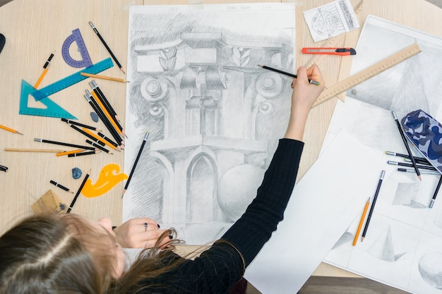 The top view of the female architect designer draws sketches in pencil on white paper.