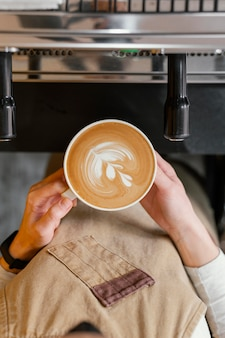 Top view of female barista holding cup of coffee