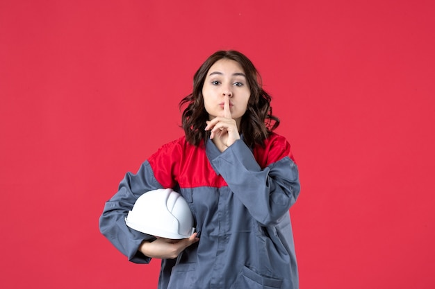 Top view of female builder in uniform and holding hard hat making silence gesture on isolated red background