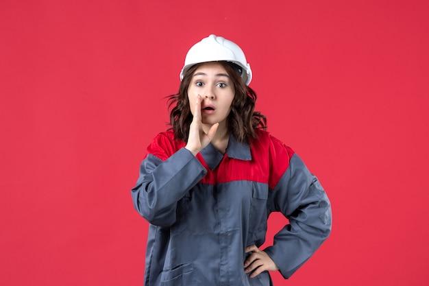 Vista dall'alto del costruttore femminile in uniforme con elmetto e chiamando qualcuno su sfondo rosso isolato