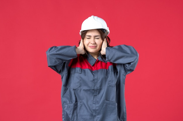 Top view of female builder in uniform with hard hat and feeling nervous on isolated red background