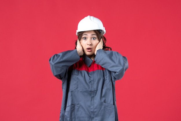 Top view of female builder in uniform with hard hat and feeling shocked on isolated red background