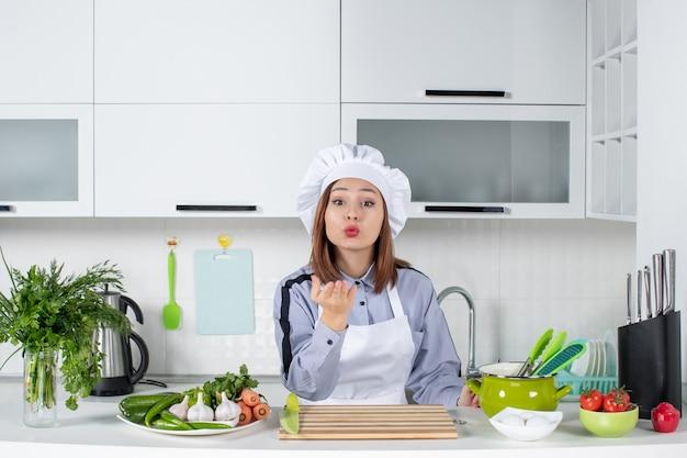 Vista dall'alto della chef donna e delle verdure fresche che fanno il gesto del bacio nella cucina bianca