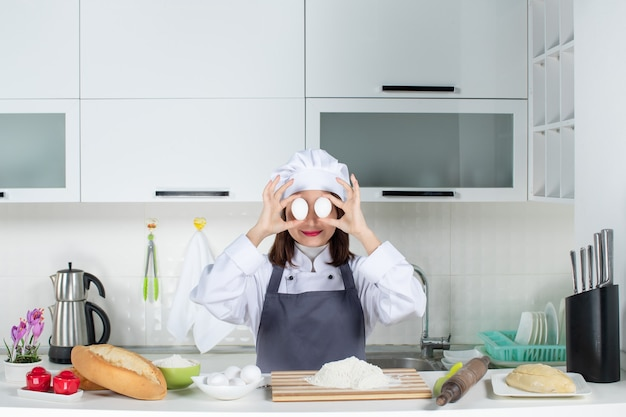 Top view of female chef in uniform standing behind the table with cutting board foods holding eggs in front of her eyes in the white kitchen