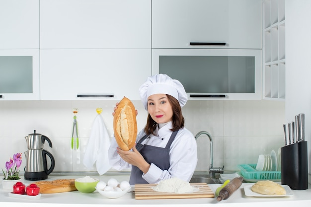 Top view of female chef in uniform standing behind the table with cutting board and foods showing bread in the white kitchen