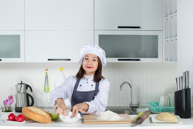Top view of female chef in uniform standing behind the table with cutting board foods taking eggs in the white kitchen